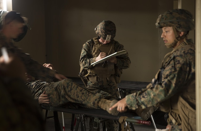 A Navy medical officer with Task Force Southwest writes down a notionally injured Marine's injuries during a mass casualty drill at forward operating base Bravo, Camp Lejeune, N.C., Feb. 28, 2017. The Marines are scheduled to deploy later this year as part of the task force to train, advise and assist the Afghan National Army 215th Corps and 505th Zone National Police in Helmand Province, Afghanistan. (U.S. Marine Corps photo by Sgt. Justin T. Updegraff)