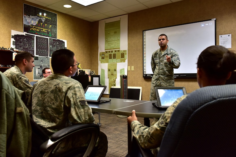 U.S. Air Force Tech. Sgt. Jose Piedra, standing, 373rd Training Squadron Detachment 4 production supervisor and instructor, goes over a final review before issuing a test to his students Feb. 23, 2017 at the Center of Excellence on Little Rock Air Force Base, Ark.  Piedra instructs more than 80 students annually in C-130J maintenance and certification.  (U.S. Air Force photo by Staff Sgt. Jeremy McGuffin)