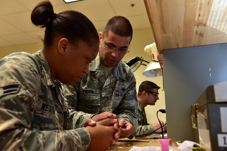 U.S. Air Force Tech. Sgt. Jose Piedra, center, 373rd Training Squadron Detachment 4 production supervisor and instructor, demonstrates splicing and building a 1553B databus cable to Airman 1st Class Shania Westin, left, 373rd TRS student, for the C-130J Feb. 23, 2017 at the Center of Excellence on Little Rock Air Force Base, Ark.  The Airman must understand how the cable functions as it transfers information throughout the aircraft and be able to build new ones effectively. (U.S. Air Force photo by Staff Sgt. Jeremy McGuffin)