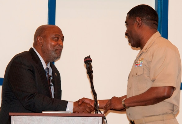 "DAHLGREN, Va. - Capt. Godfrey ""Gus"" Weekes, Naval Surface Warfare Center Dahlgren Division (NSWCDD) commanding officer, presents the Dahlgren history book, ""The Sound of Freedom,"" to Dr. Jeremiah Williams - President of the 100 Black Men of America Inc., Virginia Peninsula Chapter - at the 2017 African American and Black History Month Observance, Feb. 28. ""I didn't realize how smart I was until I joined the Navy,"" said Williams. ""The recruiter told me I qualified for every program the Navy offers. When I went to nuke (Nuclear Power) school, and among the last ones standing, I felt I could conquer the world. The Navy saved me and I appreciated that.""  (U.S. Navy Photo by George Smith/Released)"