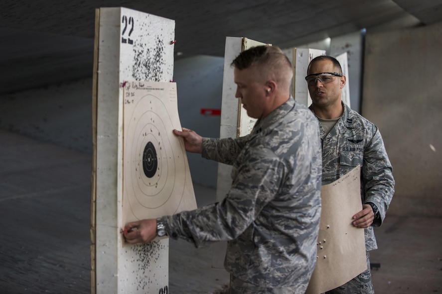 Two competitors collect their score sheets after participating in the Pistol Excellence in Competition March 2, 2017, at Cannon Air Force Base, N.M. Competitors who scored in the top 10 percentile received the Pistol EIC badge. (U.S. Air Force photo by Senior Airman Luke Kitterman/Released)