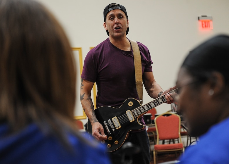 Former Korn guitarist and Rock to Recovery founder Wes Geer shouts pointers to Air Force Wounded Warrior Trials participants while playing the guitar during a Rock to Recovery practice session in Las Vegas, March 1, 2015. Geer played guitar during two interactive music sessions with AFW2 Trial's band, and helped the group perform their song in front of family and friends during the games' post-event banquet. (U.S. Air Force photo by Staff Sgt. Siuta B. Ika)