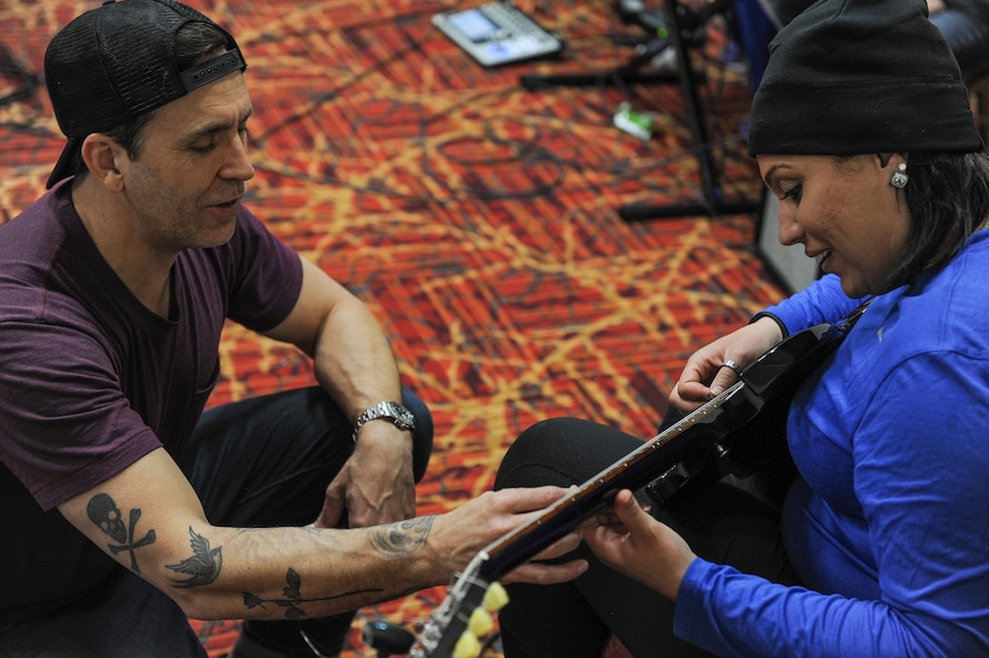 Former Korn guitarist and Rock to Recovery founder Wes Geer gives pointers to an Air Force Wounded Warrior Trials participant during a Rock to Recovery practice session in Las Vegas, March 1, 2015. Rock to Recovery brings together people suffering from similar ailments and each participant shares their personal story before choosing from a variety of instruments to play as part of a band. (U.S. Air Force photo by Staff Sgt. Siuta B. Ika)