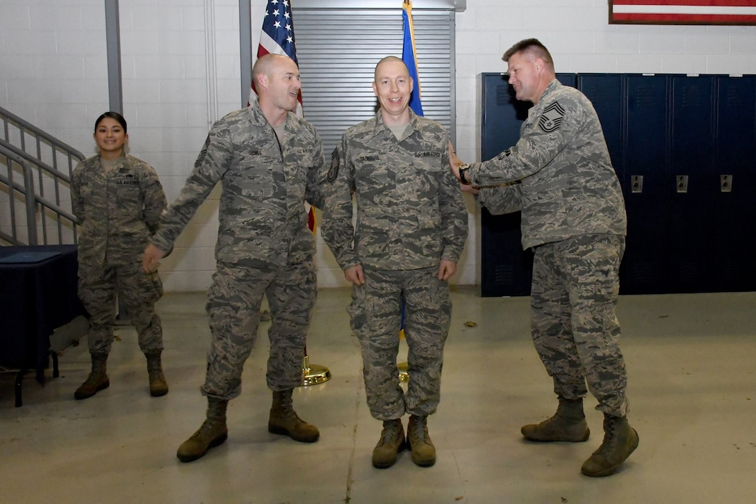 """Chief Master Sgt. Glen F. Saunders Jr., quality assurance superintendent with the 94th Maintenance Group, is """"patched"""" by Chief Master Sgt. Christopher Sokolick, maintenance superintendent with the 94th MG, and Chief Master Sgt. Marvin Jones, maintenance operations superintendent with the 94th MG, during his promotion ceremony March, 5, 2017 at Dobbins Air Reserve Base, Georgia. (U.S. Air Force photo/Airman 1st Class Justin Clayvon)"""