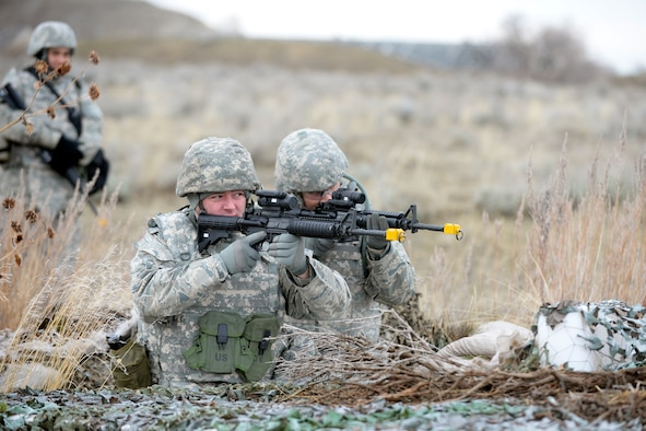 Tech. Sgts. Vincent Bourgeois and Michael Curtin, 729th Air Control Squadron, practice site perimeter defense during expeditionary training Feb. 22 at Hill Air Force Base. The four-day pre-deployment exercise covered personal preparation, site preparation and defense, weapons familiarization, self-defense, care-under-fire, improvised explosive device classification and communication. (U.S. Air Force photo by Todd Cromar)