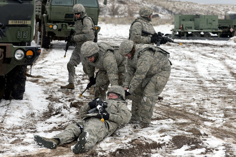Airman 1st Class Paul Leszczewski and Senior Airman Kristina Stubbe, 729th Air Control Squadron, drag a simulated wounded Airman, Senior Airman Thomas Smith, while practicing site defense during a expeditionary training exercise Feb. 23. (U.S. Air Force photo by Todd Cromar)