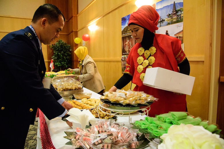 Indonesian Foreign Liaison Officer Maj. H. L. Tobing and spouse, Shinta, place food on the table representing their country during the International Buffet at Hill Air Force Base, Utah, March 1, 2017. The annual event offers Foreign Liaison Officers and their families to share their food and culture with colleagues and friends. (U.S. Air Force photo/R. Nial Bradshaw)