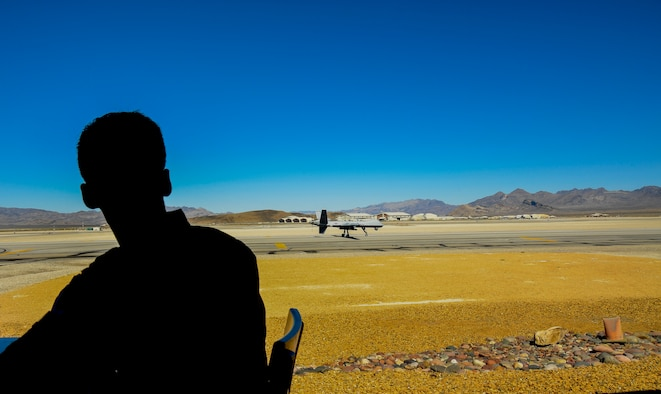 An Airman assigned to the 11th Attack Squadron watches an MQ-9 Reaper land on the runway March 3, 2017, at Creech Air Force Base, Nev. The 11th ATKS became the first remotely piloted aircraft squadron in the Air Force in 1995 and continues to conduct MQ-1 Predator and MQ-9 Reaper aircrew launch and recovery training today. (U.S. Air Force photo illustration/Airman 1st Class James Thompson)