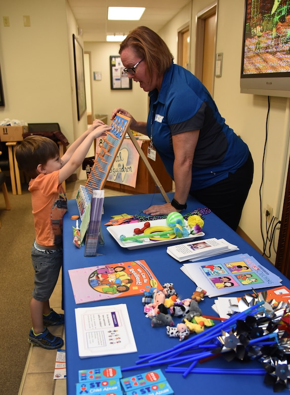 Debra Thomas, Families OverComing Under Stress family resilience coordinator, assists Thomas Hull, son of Master Sgt. Shawn Hull, 81st Dental Squadron dental lab NCO in charge, with a game during the 7th Annual Give Kids a Smile Day at the dental clinic March 1, 2017, on Keesler Air Force Base, Miss. The event was held in recognition of National Children's Dental Health Month and included free dental exams, radiographs and cleanings for more than 95 children age 2 and older. (U.S. Air Force photo by Kemberly Groue)