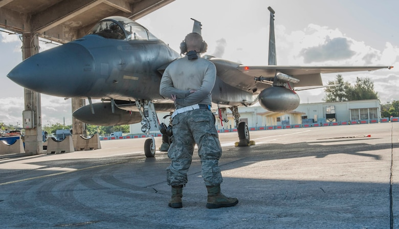 U.S. Air Force Senior Airman Vincent Hassing, a 44th Aircraft Maintenance Unit maintainer, waits as an F-15 Eagle prepares to taxi to the runway, Feb. 14, 2017, on Kadena Air Base, Japan. The 44th AMU and members of the 44th Fighter Squadron participated in an exercise alongside members of the U.S. Navy 27th and 102nd Strike Fighter Squadrons from Naval Air Station Atsugi, Japan. (U.S. Air Force photo by Senior Airman Nick Emerick/Released)