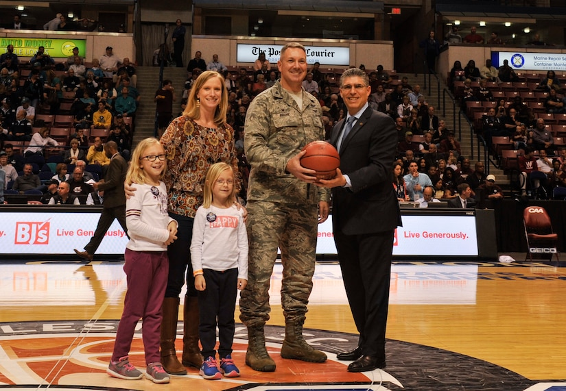 Mr. Joseph D'Antonio, Colonial Athletic Association Commissioner, right, presents Air Force Col. Robert Lyman, Joint Base Charleston commander, center, and his family an autographed basketball during the 2017 CAA Men's Basketball Championship, March 5, 2017, at the North Charleston Coliseum, South Carolina. The presentation recognized and honored the men and women of Joint Base Charleston and their service to the community and nation.