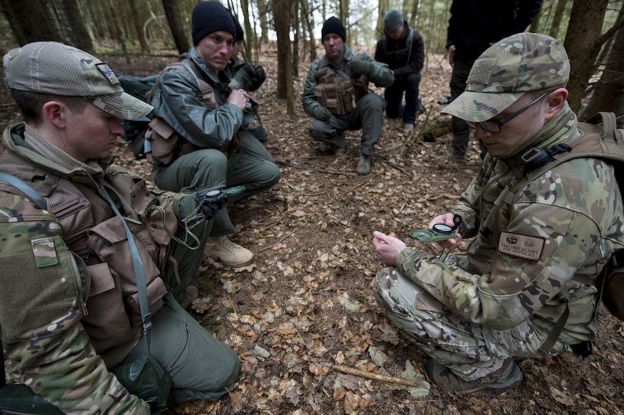 U.S. Air Force Staff Sgt. Corey Dilport, right, 52nd Operations Support Squadron Survival, Evasion, Resistance and Escape specialist, demonstrates compass use during SERE training near Spangdahlem Air Base, Germany, March 3, 2017. The curriculum taught at SEAR trains pilots how to react in the event their aircraft is downed and has three key parts: survival and evasion, resistance and escape, and water survival. (U.S. Air Force photo by Airman 1st Class Preston Cherry)