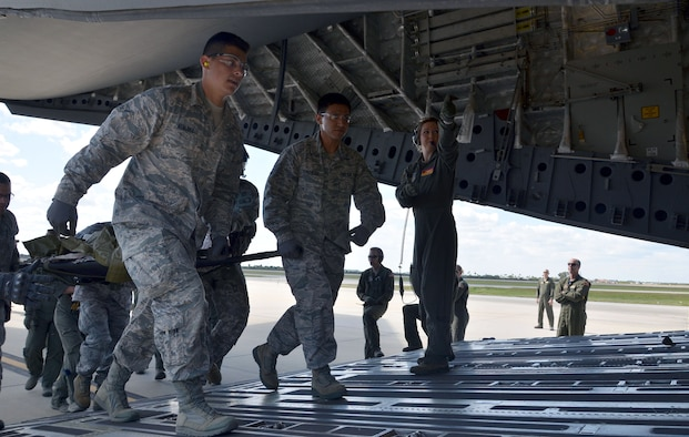Airman Michael Alvarez, left, and Staff Sgt. Roberto Gonzalez, center, both reservists with the 920th Aeromedical Staging Squadron, load a simulated patient onto a C-17 Globemaster III during the fifth annual MEDBEACH joint medical response exercise March 5, 2017 at Patrick Air Force Base, Florida. The C-17 and an Army National Guard UH-60 Black Hawk were flown in to provide a staging platform for stabilization and transport of battlefield-injured service members. (U.S. Air Force photo/Capt. Leslie Forshaw)