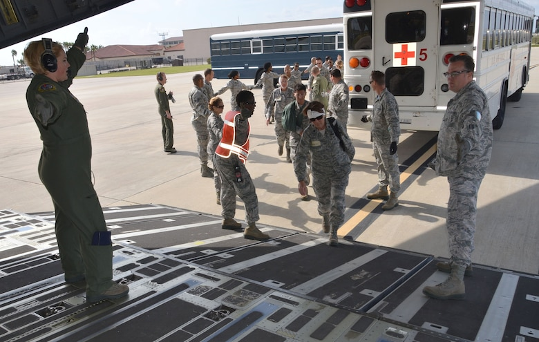 Simulated ambulatory patients are guided up the ramp of a C-17 Globemaster III aircraft March 5, 2017 during the 5th annual MEDBEACH joint medical response exercise at Patrick Air Force Base, Florida. The C-17 was flown in to provide a staging platform for stabilization and transport of battlefield-injured service members. (U.S. Air Force photo/Capt. Leslie Forshaw)