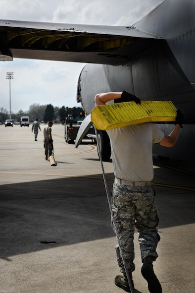 An Airmen carries a chock for Aircraft 0049 at Barksdale Air Force Base, La., Feb. 28, 2017. The aircraft will be disassembled then transported to Davis Monthan AFB, as a part source for the flying fleet. (U.S. Air Force photo/Airman 1st Class Stuart Bright)