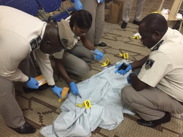 Members of the Burkina Faso National Police attend to a crime scene during the practical exercise portion of the Law Enforcement Investigative Skills Exchange Program, the first-ever Air Force Office of Special Investigations strategic engagement in the West African country, formerly known as Upper Volta. (U.S. Air Force photo/25 EFIS)