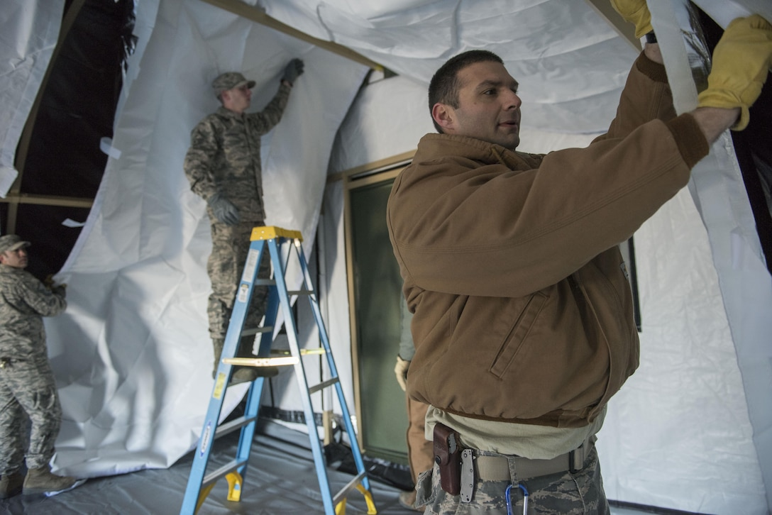 Members of the 366th Civil Engineering Squadron finish applying the inner lining of a tent Mar. 2, 2017, at Mountain Home Air Force Base, Idaho. Several tents were erected throughout the morning as part of a readiness exercise. (U.S. Air Force photo by Senior Airman Connor Marth/Released)