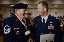 Retired U.S. Air Force Master Sgt. E.J. Adams shakes hands with Col. Ty Neuman, 2nd Bomb Wing commander, during the 38th Annual Veterans' Luncheon at Barksdale Air Force Base, La., March, 3, 2017. The luncheon is held annually to honor prisoners of war and veterans of WWII, the Korean War and Vietnam. (U.S. Air Force photo/Senior Airman Mozer O. Da Cunha)