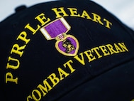 A Purple Heart Combat Veteran baseball cap rests at a table during the 38th Annual Veterans' Luncheon at Barksdale Air Force Base, La., March, 3, 2017. The Purple Heart is awarded to members of the armed forces of the U.S. who are wounded by an instrument of war in the hands of the enemy and posthumously to the next of kin in the name of those who are killed in action or die of wounds received in action. It is specifically a combat decoration. (U.S. Air Force photo/Senior Airman Mozer O. Da Cunha)