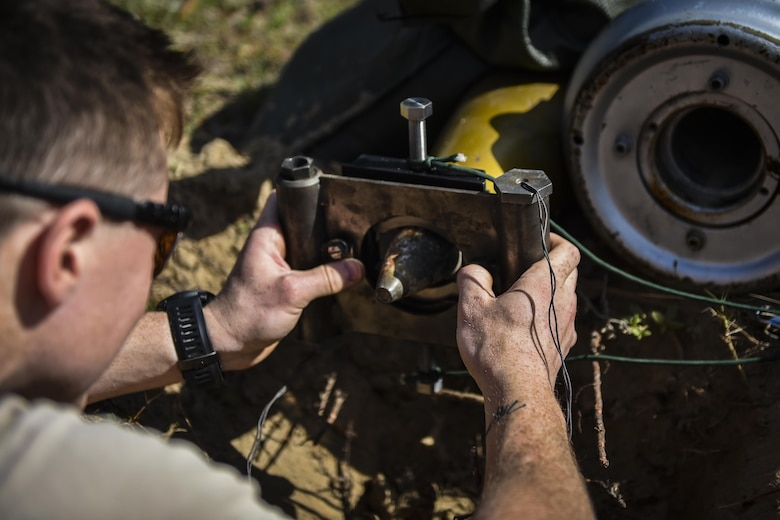 Airman 1st Class Lawrence Gress, an explosive ordinance disposal journeyman with the 1st Special Operations Civil Engineer Squadron, secures a MK1 rocket wrench on the fuse of a projectile during EOD tool training at Hurlburt Field, Fla., Mar. 6, 2017. If the rocket wrench is not straight, it may not properly remove the fuse and could cause damage to the tool. (U.S. Air Force photo by Airman 1st Class Joseph Pick)