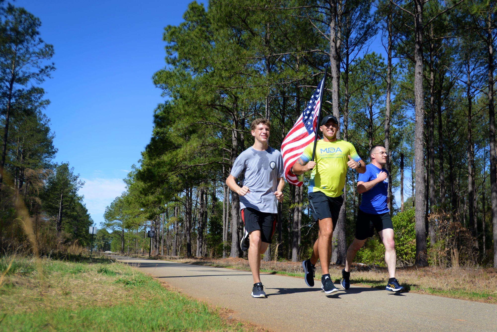"""U.S. Air Force Senior Airman Michael Hall, 20th Aerospace Medicine Squadron flight and operation medical technician, center, runs alongside two other participants in a 5K at Shaw Air Force Base, S.C., Feb. 25, 2017. The Muscular Dystrophy Association chose Hall to represent them in the 2017 Boston Marathon on """"Team Momentum,"""" a group that encourages its members to dedicate their miles to individuals with muscular dystrophy, amyotrophic lateral sclerosis (also known as Lou Gehrig's disease) and other life-threatening diseases. Hall runs for his sister, Danielle, who has lived with muscular dystrophy for 27 years, and his brother DJ, who passed away from the disease when he was 19 months old. (U.S. Air Force photo by Airman 1st Class Kelsey Tucker)"""