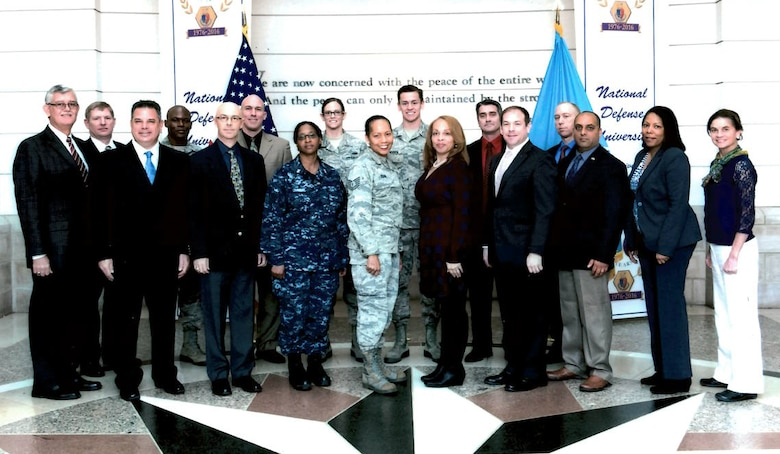Airman 1st Class Lindsey Plotner and Airman 1st Class Joseph Mousch, center, back row, are pictured with the staff and seminar leaders for the Reserve Component National Security Course at the National Defense University. Plotner and Mousch, provided administrative support for the course, an assignment much different from their primary duties as aircraft maintenance specialists.