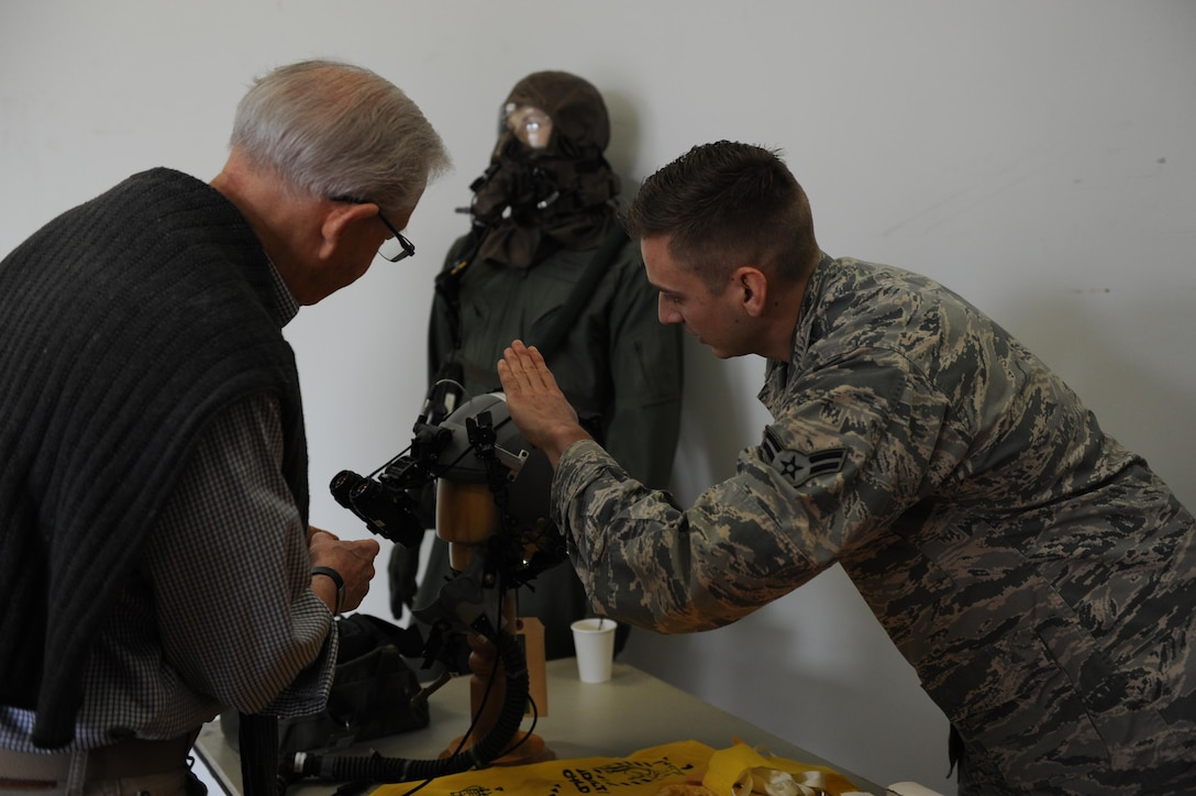 U.S. Air ForceAirman 1st Class Travis Jones, 19th Operation Support Squadron Aircrew Flight Equipment technition, shows off the nightvision goggles the pilots use to Mr. David Egan , a pilot for the 41st AS in 1963, during a reunion March 24, 2017, on Little Rock Air Force Base, Ark. The reunion honored the 75th anniversary of the 41st AS. (U.S. Air Force photo by Airman 1st Class Grace Nichols)
