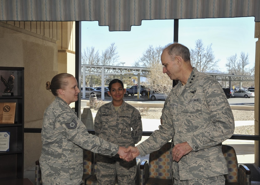 Lt. Gen. Mark Ediger, Surgeon General of the Air Force, coins Tech. Sgt. Tanya Cole, NCOIC of the Dental Squadron during a visit to Kirtland Air Force Base March 2. Ediger recognized several members of the MDG team for being outstanding professionals in their career fields.