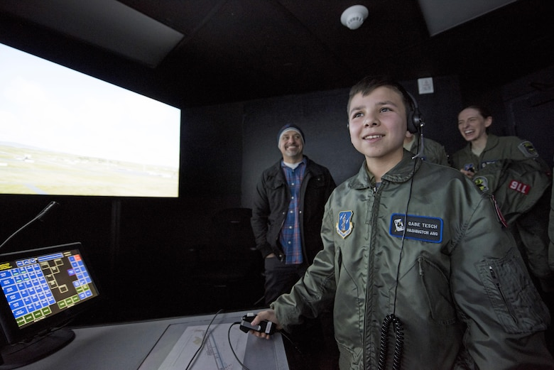 """Pilot for a Day"" candidate Gabe Tesch issues landing instructions to a virtual pilot during his visit to the air traffic control simulator Mar. 1, 2017, at Fairchild Air Force Base, Washington. Gabe spent the day visiting several work centers throughout the base receiving hands on instruction and briefings on what it takes to be a KC-135 Stratotanker pilot. The ""Pilot for a Day"" program provides disadvantaged or seriously ill children a chance to spend the day with members of the Washington Air National Guard training as an honorary pilot. (U.S. Air Force photo by Master Sgt. Michael Stewart/Released)"