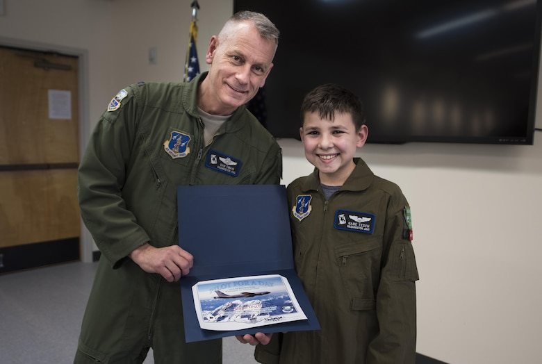 "Col. Daniel Swain, 141st Air Refueling Wing commander, presents ""Pilot for a Day"" candidate Gabe Tesch with his pilot completion certificate Mar. 1, 2017, at Fairchild Air Force Base, Washington. Gabe spent the day visiting several work centers throughout the base receiving hands on instruction and briefings on what it takes to be a KC-135 Stratotanker pilot. The ""Pilot for a Day"" program provides disadvantaged or seriously ill children a chance to spend the day with members of the Washington Air National Guard training as an honorary pilot. (U.S. Air Force photo by Master Sgt. Michael Stewart/Released)"