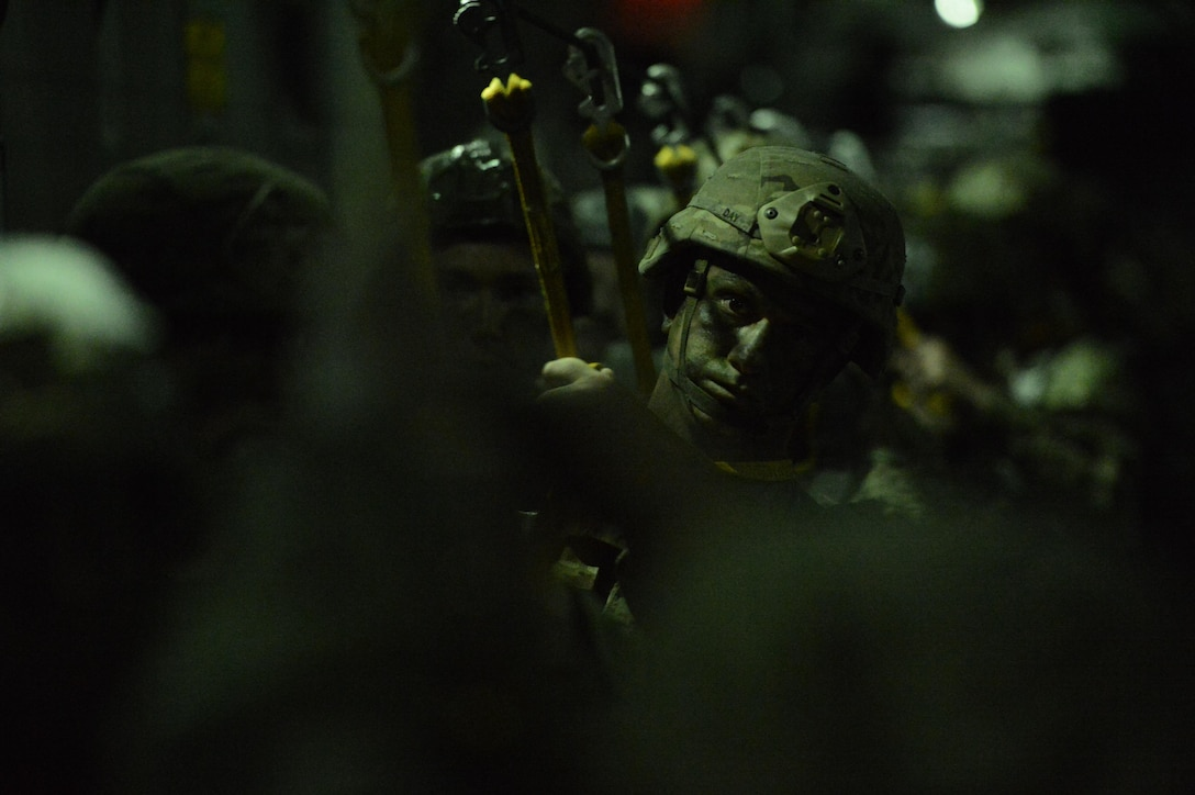 """A U.S. Army paratrooper from the 82nd Airborne Division prepares for the green """"jump"""" light prior to a static line jump from a McChord C-17 Globemaster III March 3, 2017, somewhere over Fort Bragg, N.C. The late-night jump took place in darkness in order to exercise a tactical, nighttime infiltration into enemy territory. (U.S. Air Force photo by Master Sgt. Sean Tobin)"""
