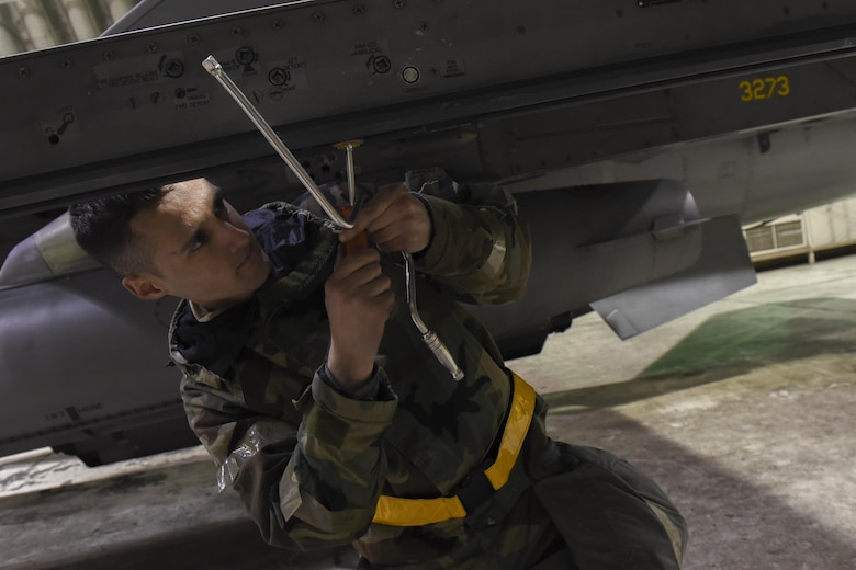 U.S. Air Force Airman 1st Class Reagan Bounner, 80th Aircraft Maintenance Unit weapons load crew member, tightens a mount on an F-16 Fighting Falcon during exercise Beverly Pack 17-2, a no-notice training exercise at Kunsan Air Base, Republic of Korea, March 7,  2017. This exercise was conducted to enhance the readiness and proficiency of Airmen while in a simulated contingency operation. (U.S. Air Force photo by Senior Airman Michael Hunsaker/Released)