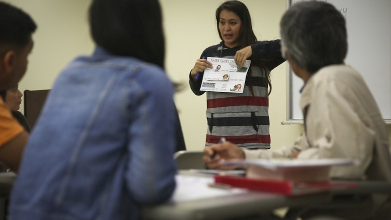 Michelle Camina, wife of Master Sgt. Anthony Camina, teaches Okinawans during the Schwab Intermediate English Class at the Education Center at Camp Schwab, Okinawa, Japan, Feb. 22, 2017. The Education Center hosts a weekly beginner and intermediate English class on Wednesdays to strengthen the bond between Okinawans and service members. The Caminas, from San Antonio, Texas, also instruct the Kin-Hansen Friendship English Class, at the Kin Town Central Community Center, Okinawa, each Tuesday. (U.S. Marine Corps photo by Lance Cpl. Andy Martinez)