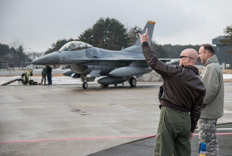 """Col. R. Scott Jobe, 35th Fighter Wing commander, displays the 14th Fighter Squadrons cheer """"wood"""" as a pilot taxis by at Misawa Air Base, Japan, March 4, 2017. The 14th FS recently returned from exercise COPE NORTH 17 at Anderson Air Force Base, Guam, it included 22 total flying units and more than 1,700 personnel from three countries. The purpose was to grow strong, interoperable relationships within the Indo-Asia-Pacific region through integration of airborne and land-based command and control assets. (U.S. Air Force photo by Senior Airman Brittany A. Chase)"""