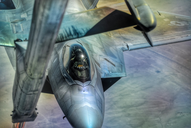 """U.S. Air Force Lt. Col. August Pfluger, 380th Expeditionary Operations Support Sq. commander and F-22 Raptor pilot, maneuvers an F-22 into position to receive fuel during an air refueling over Syria, March 3, 2017.  During the refueling Pfluger re-enlisted Staff Sgt. Rebecca Rains who was in a KC-10 Extender, next to the boom operator, while reciting the oath of enlistment over headset.  """"This was the coolest thing I've done [since joining],"""" Rains said.  """"So I get on the headset and I'm talking to him and he shared with me some background about his mission prior to coming up for fuel.  He then said 'You ready to do this?' and I said 'yep let's go.'"""""""