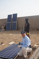 Peter Cho, an electrical engineer in the marine and aviation division at Naval Surface Warfare Center, Carderock Division, in West Bethesda, Md., prepares a solar panel to bring light to a community in the rural West African city of Mbour, Senegal. Courtesy photo
