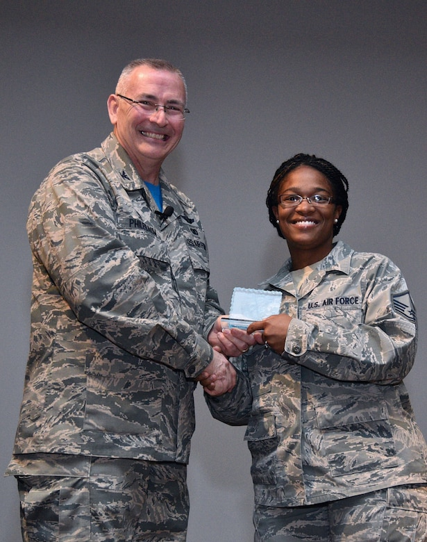 The 932nd Airlift Wing commander, Col. Jonathan Philebaum, smiles as he presents the Fourth Quarter Civilian Category II award to Master Sgt. Barbara Owens for her civilian work in the Force Support Squadron.  The event took place at his Wingman Day commander's call March 4, 2017, on Scott Air Force Base, near Belleville, Ill. They work together during the week as part of an energized team at the 932nd Airlift Wing.  The unit is part of 22nd Air Force, Air Force Reserve Command. (U.S. Air Force photo by Tech. Sgt. Christopher Parr)