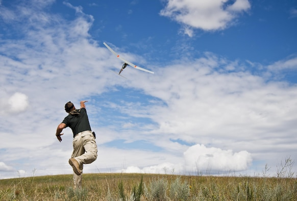 Staff Sgt. Leland Hastings, of the 919th Special Operations Security Forces Squadron, launches a Raven-B, a 4-by-4 foot unmanned aerial system, into the skies above Camp Guernsey, Wyo., Aug. 4, 2015. The 919th SOSFS brought the UAS to demonstrate its capabilities to other security forces units involved in a large field training exercise at the camp. The Raven-B has the ability to take photos, video in day or night, and even designate locations via an IR laser.  It also provides coordinates, magnetic azimuths, and linear distances creating a birds-eye view to topographical map. (U.S. Air Force photo/Tech. Sgt. Sam King)