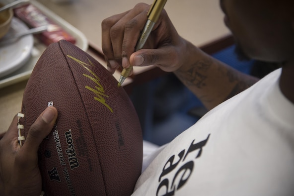 Malcolm Mitchell, New England Patriots' wide receiver and Super Bowl LI Champion, signs a football during a visit March 7, 2017, at Moody Air Force Base, Ga. Mitchell, a Valdosta native, got a glimpse of a typical day in the life of Moody Airmen. Mitchell also spent time with Airmen and signed autographs for local Patriots' fans during his visit. (U.S. Air Force photo by Senior Airman Ceaira Young)