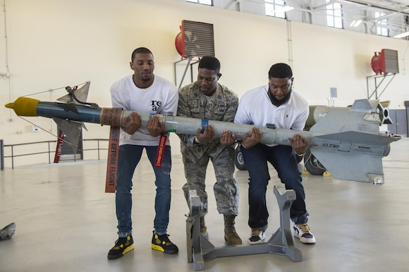 Malcolm Mitchell, left, New England Patriots' wide receiver and Super Bowl LI Champion, Capt. Eric Johnson, 23d Civil Engineer Squadron commander, and James Rome, former Pittsburgh Steeler tight end, lift an AIM 9 Sidewinder II missile during Mitchell's visit March 7, 2017, at Moody Air Force Base, Ga. Mitchell, a Valdosta native, got a glimpse of a typical day in the life of Moody Airmen. Mitchell also spent time with Airmen and signed autographs for local Patriots' fans during his visit. (U.S. Air Force photo by Senior Airman Ceaira Young)
