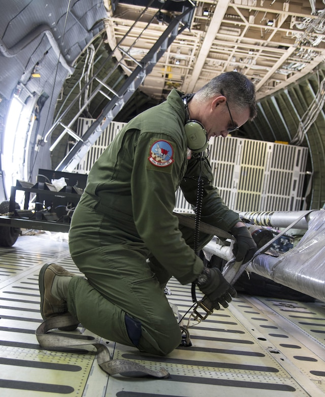Staff Sgt. Matthew Larson, 22nd Airlift Squadron, secures cargo on a C-5M Super Galaxy prior to a flight to Yokota Air Base Japan, March 4, 2017. Larson and his team of loadmasters secured approximately 70,000 pounds of cargo along with seven passengers flying Space-Avaliable travel. (U.S. Air Force photo/Staff Sgt. Nicole Leidholm)