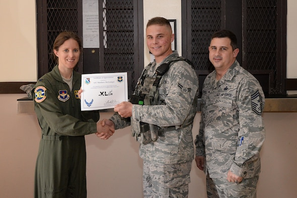 "Airman 1st Class Matthew McGonigal, 47th Security Forces Squadron patrolman (center), accepts the ""XLer of the Week"" award from Col. Michelle Pryor, 47th Flying Training Wing vice commander (left), and Chief Master Sgt. George Richey, 47th FTW command chief (right), on Laughlin Air Force Base, Texas, March 2, 2017. The XLer is a weekly award chosen by wing leadership and is presented to those who consistently make outstanding contributions to their unit and Laughlin. (U.S. Air Force photo/Airman 1st Class Daniel Hambor)"