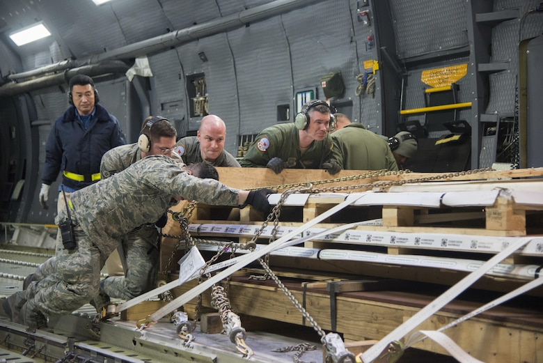 Airmen from the 22nd Airlift Squadron and the 730th Air Mobility Squadron, download cargo off of a C-5M Super Galaxy after arriving at Yokota Air Base, Japan, March 5, 2017. The team worked together to offload nearly 50,000 pounds of various cargo. (U.S. Air Force photo/Staff Sgt. Nicole Leidholm)