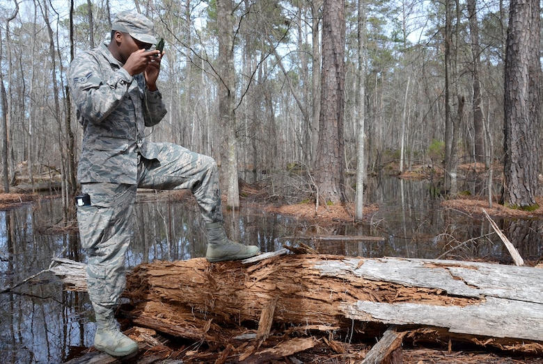 Airman 1st Class Tyzhe Speights, 51st Combat Communications Squadron, uses a lensatic compass to locate his teams designated point during a land navigation exercise with the 5th Combat Communications Group at Robins Air Force Base, Ga., March 2, 2017. The 5th CCG provides a two-week course for a maximum of 34 students and covers a variety of topics such as land navigation, improvised explosive device detection and much more. (U.S. Air Force photo by Tech. Sgt. Kelly Goonan/released)