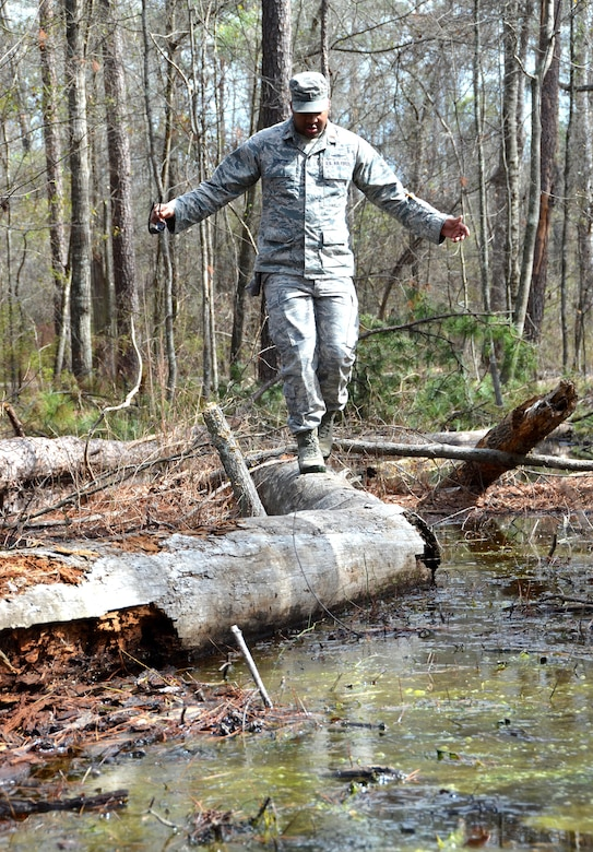 Second Lieutenant Steven Sumpter, 729th Air Control Squadron, balances himself ontop a fallen tree while navigating across a flooded area to get to the designated marker during a land navigation exercise on Robins Air Force Base, Ga., March 2, 2017. The 5th CCG provides a two-week course for a maximum of 34 students and cover a variety of topics such as land navigation, improvised explosive device detection, and much more. (U.S. Air Force photo by Tech. Sgt. Kelly Goonan/released)