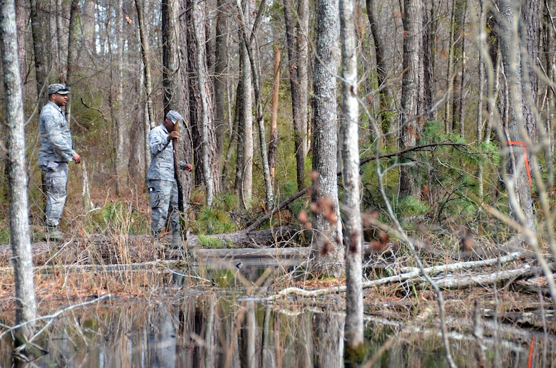 Second Lt. Steven Sumpter, 729th Air Control Squadron, and Airman 1st Class Tyzhe Speights, 51st Combat Communication Squadron, trek through a flooded area to get their designated marker during a land navigation exercise at Robins Air Force Base, Ga., March 2, 2017. The 5th Combat Communications Group provides a two-week course for a maximum of 34 students and covers a variety of topics like land navigation, improvised explosive device detection and much more. (U.S. Air Force photo by Tech. Sgt. Kelly Goonan/released)