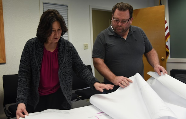 Michele Cardenas, 60th Civil Engineer Squadron operation flight deputy, and Mike West, 60th CES facility systems superintendent, review a print of the David Grant USAF Medical Center at Travis Air Force Base, Calif., March 2, 2017. Cardenas started working in the 60th CES during an initiative to hire women into craftsmen positions. (U.S. Air Force photo by Senior Airman Sam Salopek) (This image was blurred for security purposes)