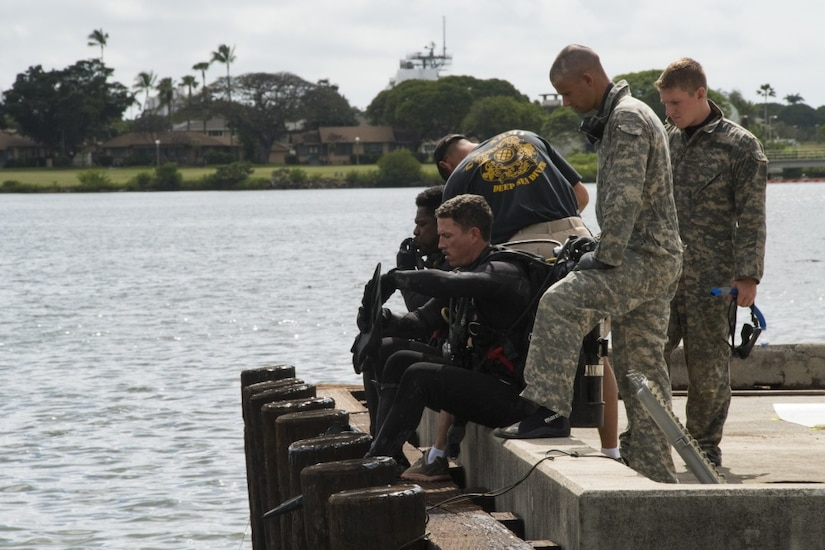Army divers assigned to 7th Dive Detachment, 84th Engineer Battalion, prepare to demonstrate repair techniques on pier support pilings, March 3, 2017.