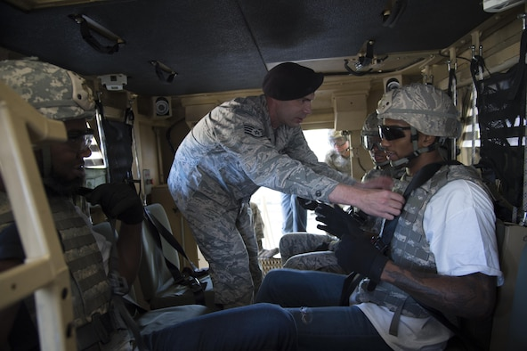 Staff Sgt. Kevin Weier, 820th Combat Operations Squadron, checks the seatbelt of Malcolm Mitchell, New England Patriots' wide receiver and Super Bowl LI Champion, prior to a rollover demonstration in the Mine-Resistant Ambush-Protected Egress Trainer during a visit March 7, 2017, at Moody Air Force Base, Ga. Mitchell, a Valdosta native, got a glimpse of a typical day in the life of Moody Airmen. Mitchell also spent time with Airmen and signed autographs for local Patriots' fans during his visit. (U.S. Air Force photo by Andrea Jenkins)