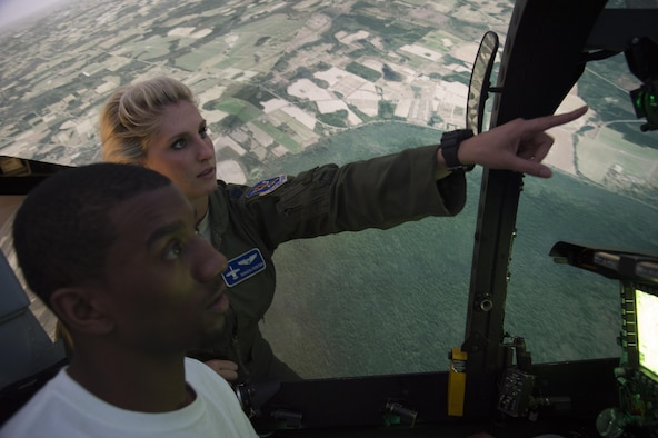 Capt. Kayla Foster, 74th Fighter Squadron A-10C Thunderbolt II pilot, gives instruction to Malcolm Mitchell, New England Patriots' wide receiver and Super Bowl LI Champion, on operating the A-10 simulator during a visit March 7, 2017, at Moody Air Force Base, Ga. Mitchell, a Valdosta native, got a glimpse of a typical day in the life of Moody Airmen. Mitchell also spent time with Airmen and signed autographs for local Patriots' fans during his visit. (U.S. Air Force photo by Andrea Jenkins)
